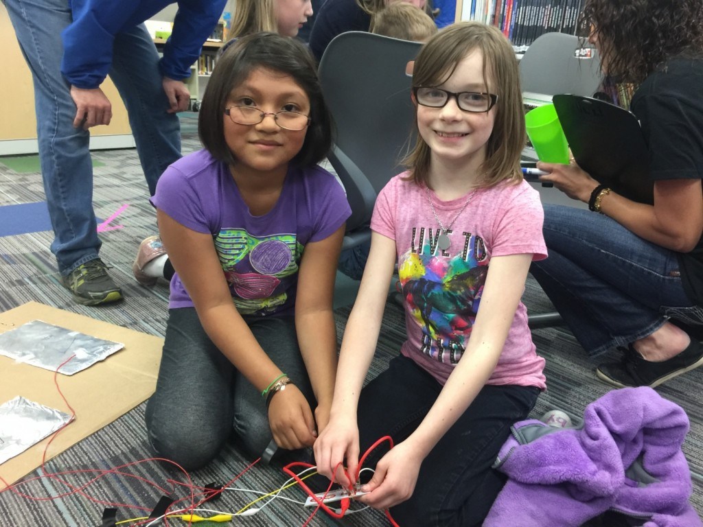 Sammy Hernandez (L) and Lizzy Witcher adjust cables connecting circuits for their foot-pad-operated math game at the Edwards FAB Faire, May 14.